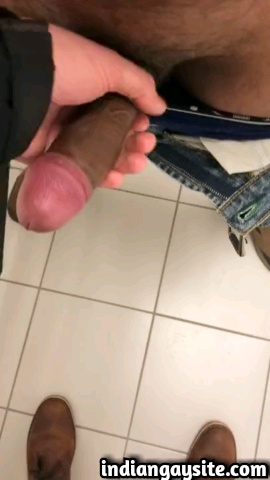 Amateur gay video of a horny desi hunk getting a handjob from a white guy in the toilet