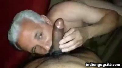 Gay silver daddy sucking a twink's hard uncut cock