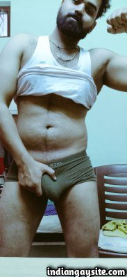 Nude hairy hunk showing off big bulge in tiny briefs