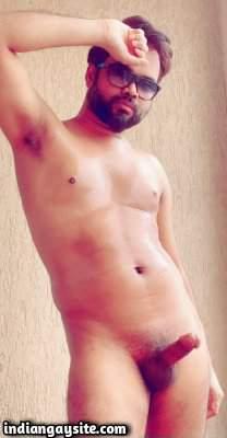 Naked hunky model posing with a big hard boner